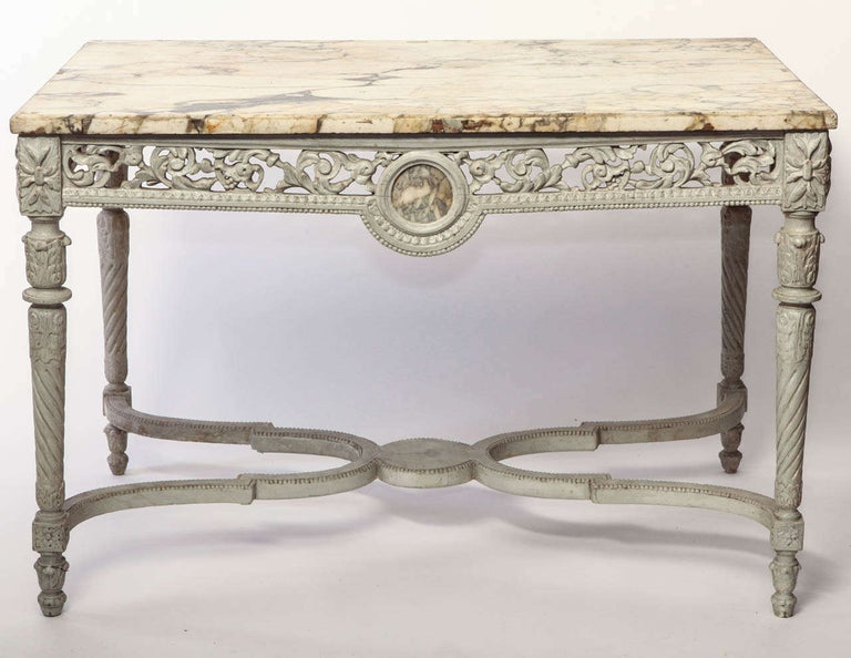 Elegant French 19th century finely carved and ivory painted center table with breche marble top.
