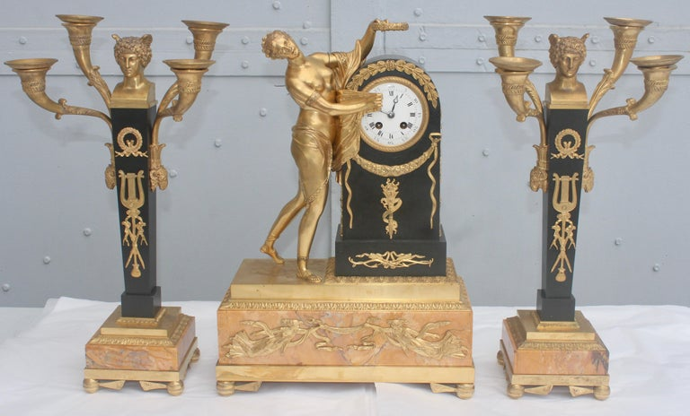 A mid-19th French ormolu and patinated bronze three-piece Clock Garniture  Composed a green patinated, chiseled and gilt bronze Mantel clock and a matching pair of four-lights candelabras,  The clock representing Psyché with the time unveiled, the