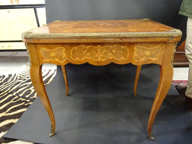 Amazing game table or card table in inlaid wood with flowers and garlands, embellished with bronzes in all the contour as well as the flaps of the legs. It has a drawer and turning it opens to use it for the use it is prefered.