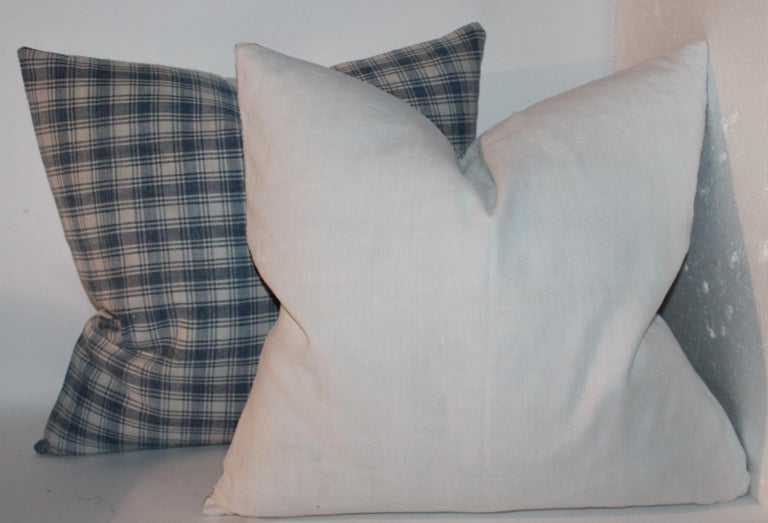 19th century blue and white linen pillows with white linen backings. Down and feather fill. Sold as a pair.
