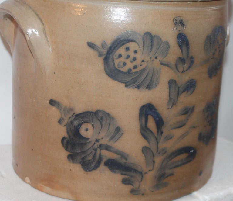 This fine double handled blue decorated stone ware crock is in good condition with minor chip on interior. There is an embossed three above the hand painted and decorated flowers on the face of the crock.