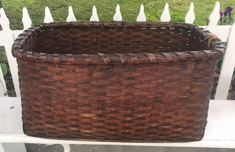 19th century early gathering basket From New England in very good condition. Minor loss on top reverse side of basket. This monumental basket has a wonderful aged patina and never had handles. It is very nice interesting construction with finger