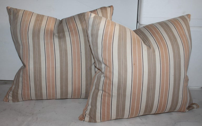 These early 19thc pastel ticking both front and back pillows are in fine condition. The inserts are down & feather fill. Selling as a collection of four pillows. Two matching pairs.
