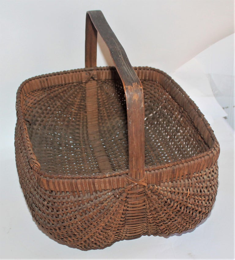 19th century early tightly woven basket with original handle. The condition is very good.