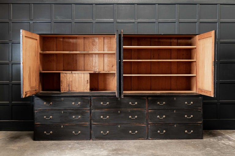 Circa. 1840  19thC English large Country House ebonised housekeepers cupboard.  Twin door cupboards sat upon a full length plank top, supported by a trio of three drawer chests, each with original brass swan neck handles and brass