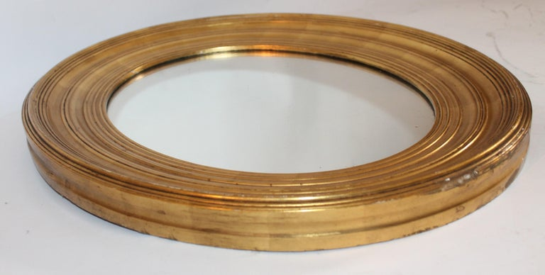 19th century original gold surface round mirror. This wired mirror is in good condition and has minor wear on the edge of the base of the mirror.