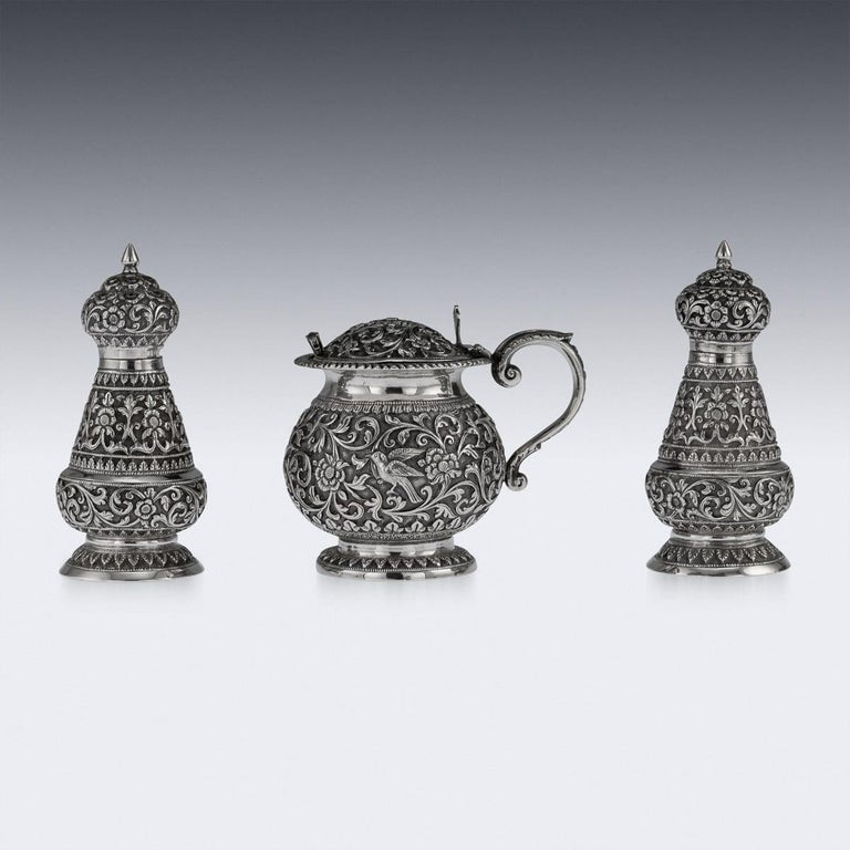 Antique late 19th century Indian solid silver repousse three-piece condiment set, comprising of a lidded mustard pot with spoon, salt and pepper shakers, each piece is profusely and beautifully repousse' decorated with scrolling foliage and flowers