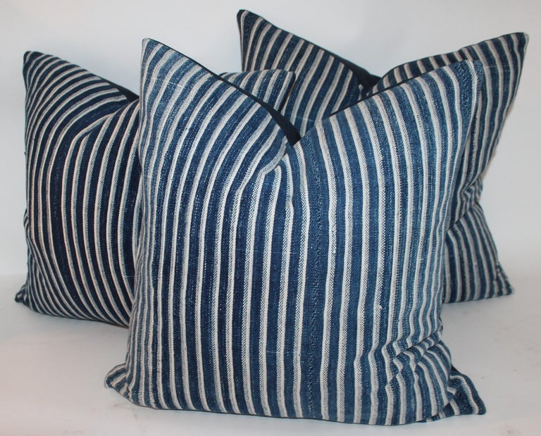 Collection of three deep blue striped linen ticking pillows. The backings are in dark blue cotton linen fabric. The inserts are down and feather fill.