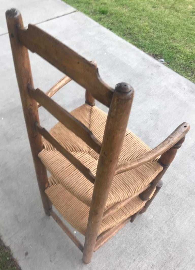 19th century ladder back double seat high chair. Believed to be used as a child's barber seat. Early English chair with woven rush seats. This is such a cool folky side chair not sure of its exact purpose.