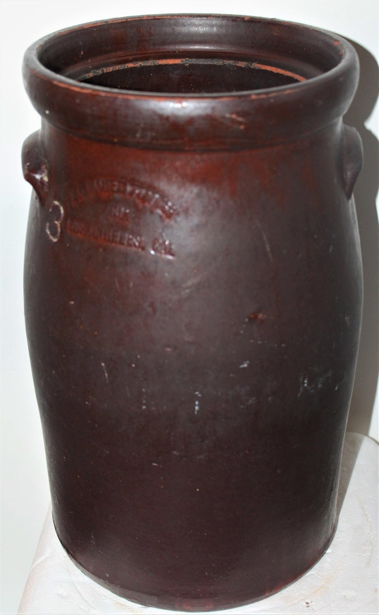 This 19th century red cay glazed crock has double handles and is signed Los Angeles. It has double handles and a chocolate brown finish. The condition is good and it is signed LA BAUER & BAUER / LOS ANGELES.