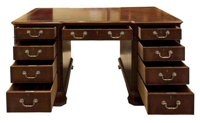 19th century mahogany desk. Inverted breakfront with canted corners shaped bracket feet with skirting reveal. Hand dyed and tooled leather insert,