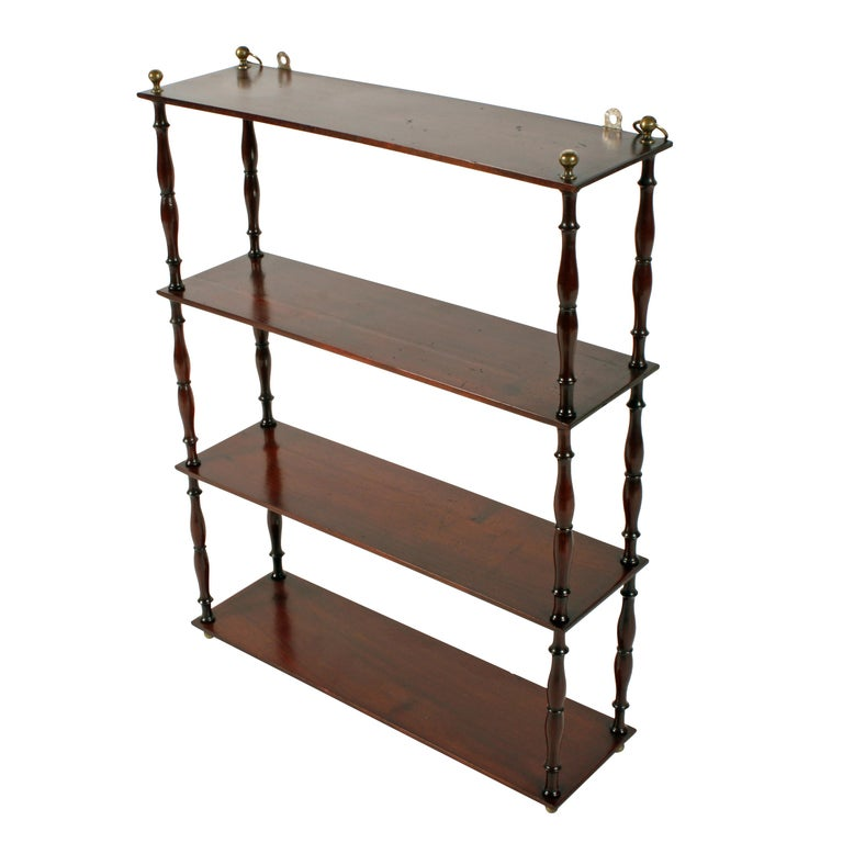 Middle of the 19th century Victorian mahogany four shelf wall hanging shelves.   The four oblong solid mahogany shelves are supported on finely turned and shaped pillars with a brass ball finial at the top.   The top shelf has brass rings from