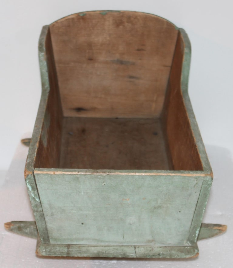 This fine handmade original blue/green doll cradle is in fine condition. It is a dry original first coat of paint and square nail construction. Fantastic form and undisturbed surface.