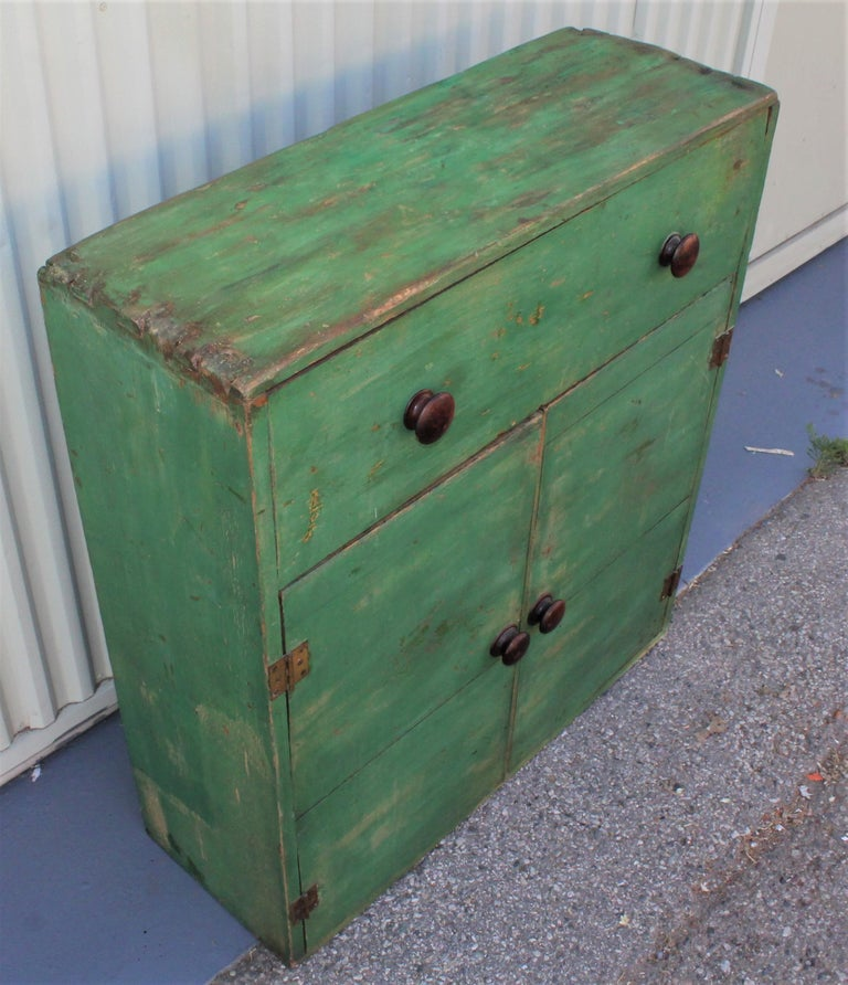 19th century original green painted dovetailed case cabinet from Pennsylvania. The condition is good with a over painted top of cabinet.