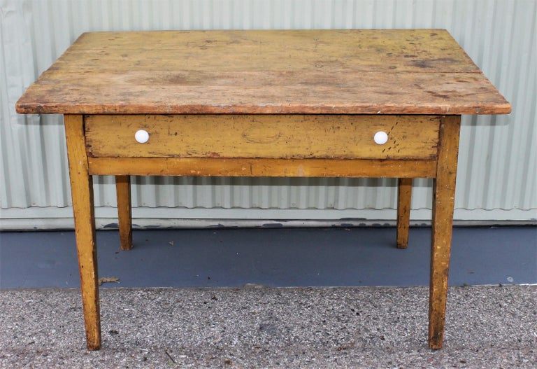 This 19th century original mustard painted farm table with large drawer. This table is square nail construction and original porcelain drawer pulls.