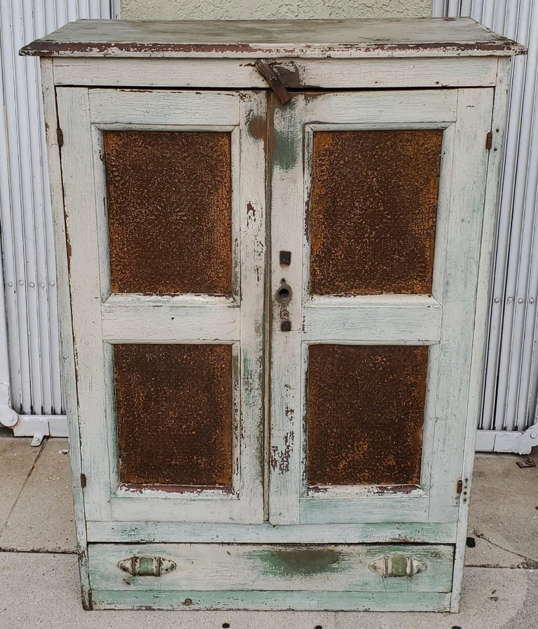 19thc original white over apple green paint and worn & aged punched tin panels. This pie safe is from East Tennessee and is in old original white painted interior as well. This pie safe came right off the farm. The condition is very good with the