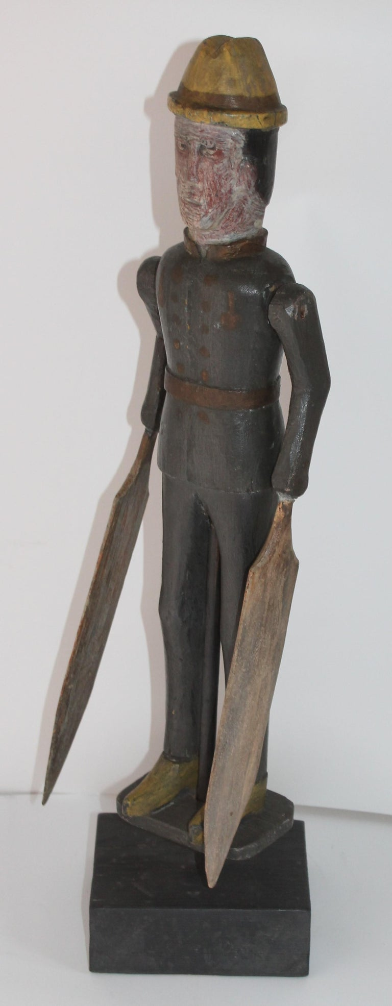 This amazing original painted folky whirlygig of a soldier is in good condition and on a block of wood that is its stand. The original blades have been re-glued at one time, but are also original to the piece. The carving is very crude with a nice