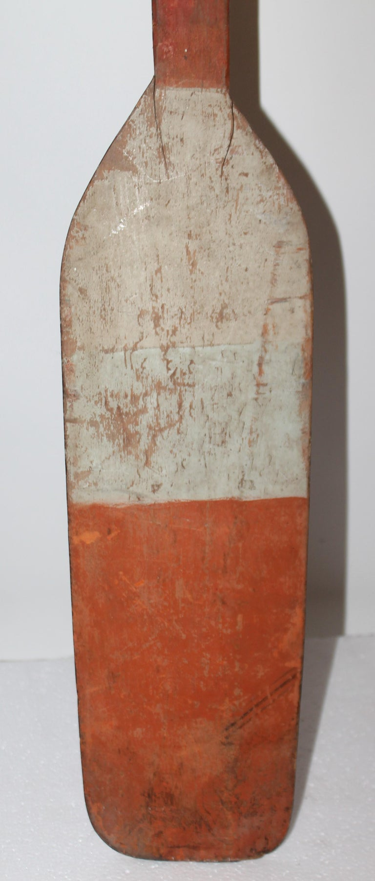 This cool 19thc orange & white painted paddle in fine condition.Great on the wall in a beach house or cottage.