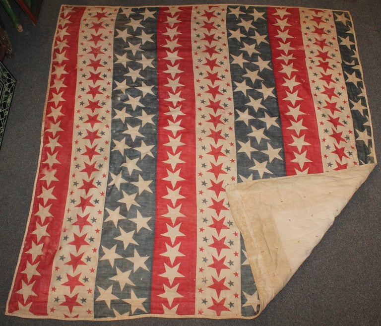 19th century Patriotic bunting red, white and blue stars tied quilt. It is dated on the feed sack back 1898. This quilt has some minor wear holes and spotting on the reverse but in pretty good condition other wise.