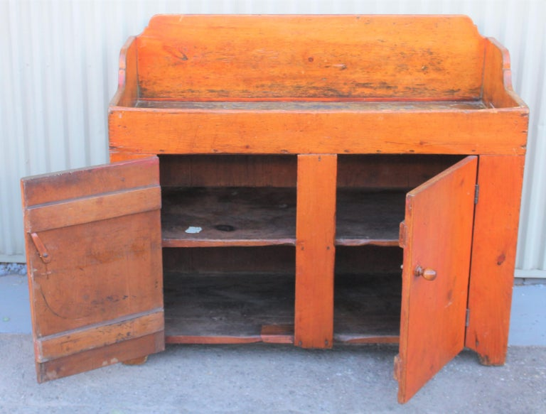 This fantastic dry sink is from Lancaster County, Pennsylvania and has two doors and two interior shelf's. The large mushroom pulls are original. The interior deep sink has a sage green original interior and was entire dry sink had a red wash on at