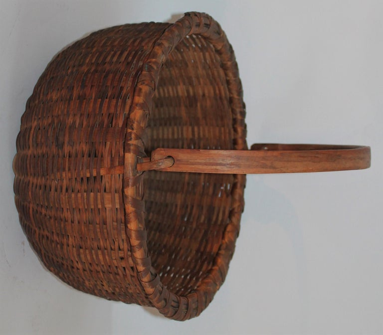 19th century handwoven basket from New England in a Shaker style format. The basket has the original kick up bottom and the original hand carved handle. The condition is pristine.