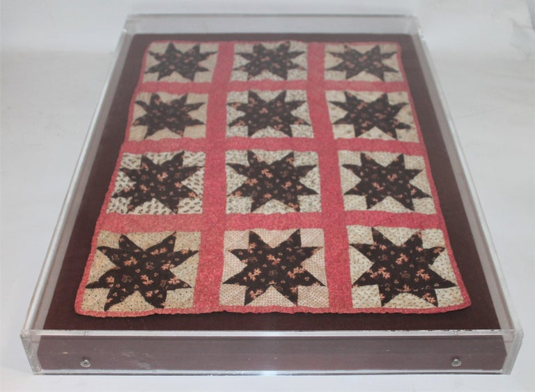 This super rare doll quilt is in great condition and is prof. mounted in a plexy. Amazing color and six point star contained within the lines. Made from cotton and placed on a custom made linen stretcher.