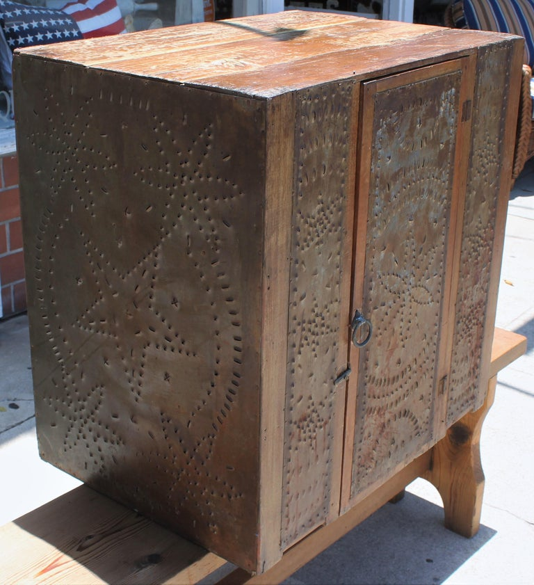 This fantastic table top punched tins pie safe that was found in East Tennessee is in fine condition. The door and shelf's are all in good condition.