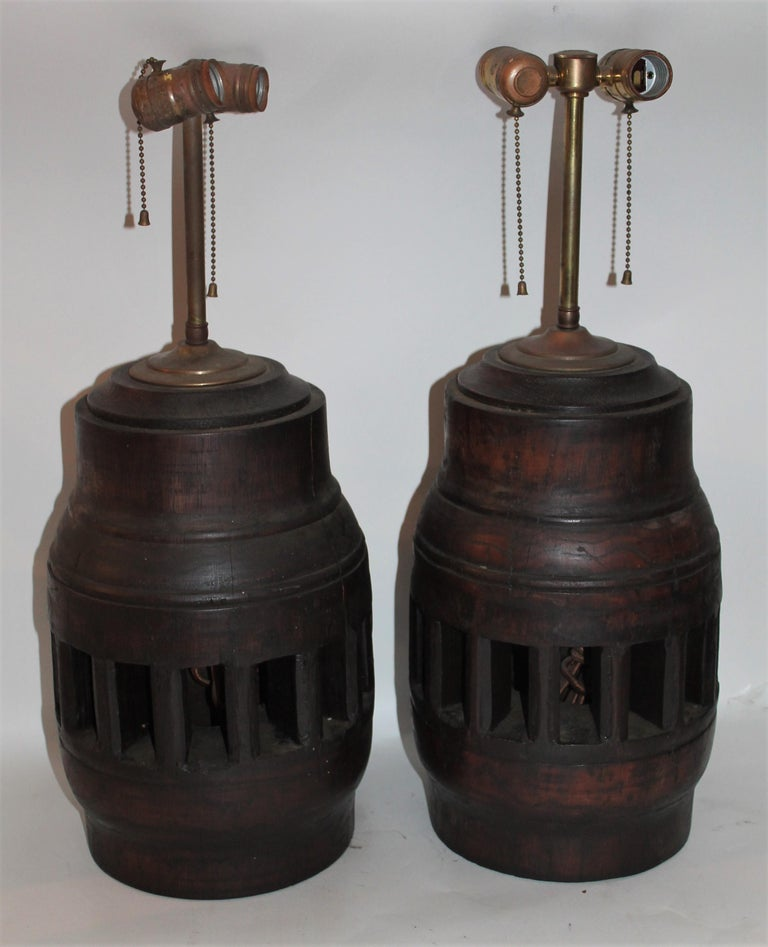 These newly wired wagon wheel hub table lamps are in as found condition. The top cap and lamp rods are in brass.   Fantastic pair of folky lamps in working condition.
