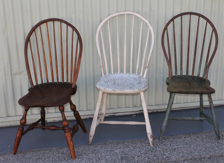 These amazing all original painted Windsor chairs are in good condition and have a wonderful worn and aged patina. The three chairs are in very good sturdy condition. The blue painted chair has a amazing patina and well worn seat. The white painted