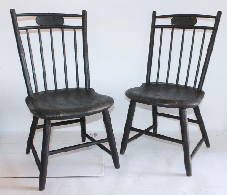 19th century original black painted children's chairs in fantastic condition. These wonderful handmade Windsors have saddle seats and were found in New England. Its so wonderful to have a matched pair of Children's Windsors in old black painted