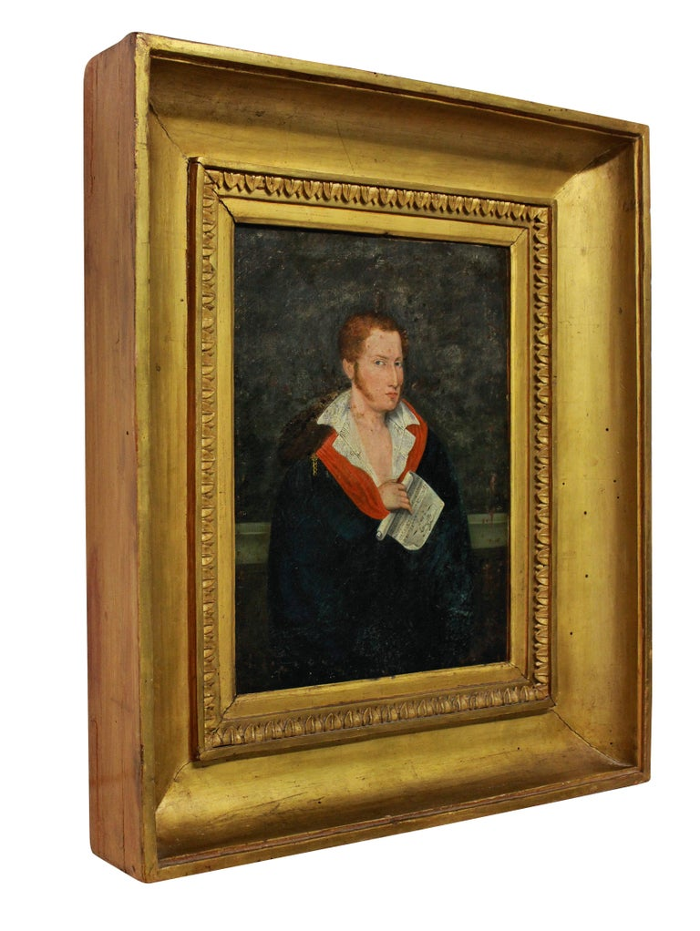 A French 1st Empire oil painting of an enigmatic red haired young man in aristocratic clothing. He clutches a musical manuscript. The water gilded frame is the original and the canvas has been laid on to board at some stage.