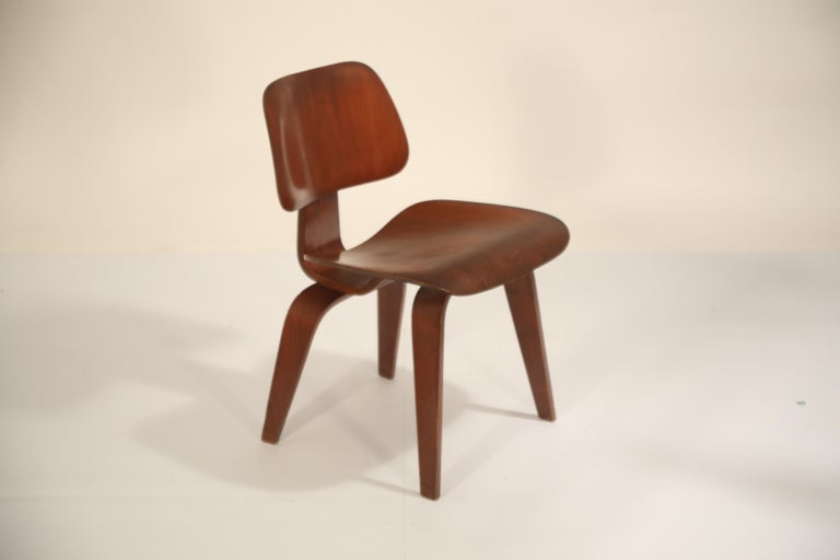 This incredible signed collector's piece is a 1st Generation DCW (Dining Chair Wood) Chair by Charles and Ray Eames, manufactured by Evans Products Company and distributed by Herman Miller. The two part label underneath the chair displays both Evans