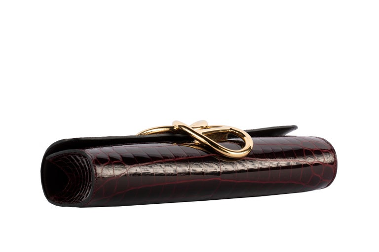 1stdibs Exclusives From Three Over Six  Brand: Hermès  Style: Egee Size: 25.4 L x 11.43 D x 5.08 H cm Color: Bordeaux Leather: Shiny Niloticus Hardware: Gold Year: 2016 X  Condition: Pristine, never carried: The item has never been carried and is in