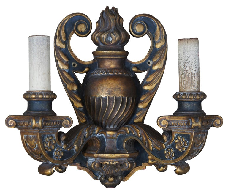 Circa 1910 Baroque Revival electric wall sconces in the shape of black and gold (Dore) wall mounted candlesticks decorated with leaves, flowers and a flaming urn.