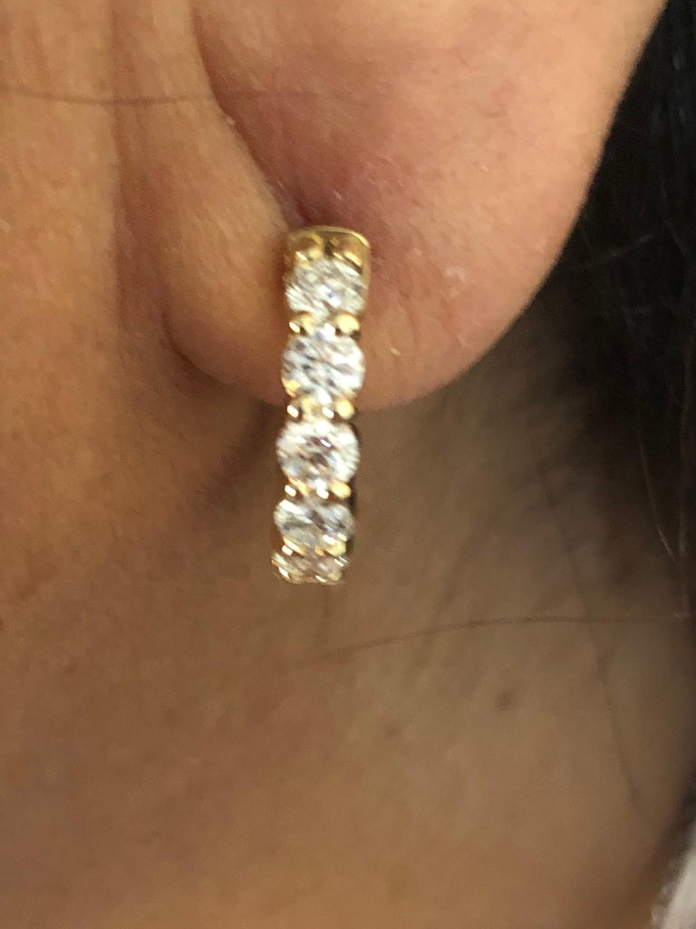 Diamond huggies set in 14K yellow gold. The total weight of the huggies is 2.00 carats. The earrings are set with 10 stones on the outside each weighing 0.20 carats. The color of the stones are G, the clarity is SI1. The diameter is 1/2 an inch. The