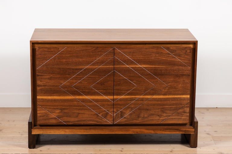 The 2-door platform chest features a solid American walnut or white oak front, base and scribed doors. Shown here in light walnut.  Available to order in various finishes with a 10-12 week lead time.