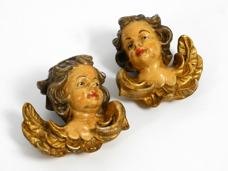 2 lovely little handmade wooden angel heads from the 1930s.