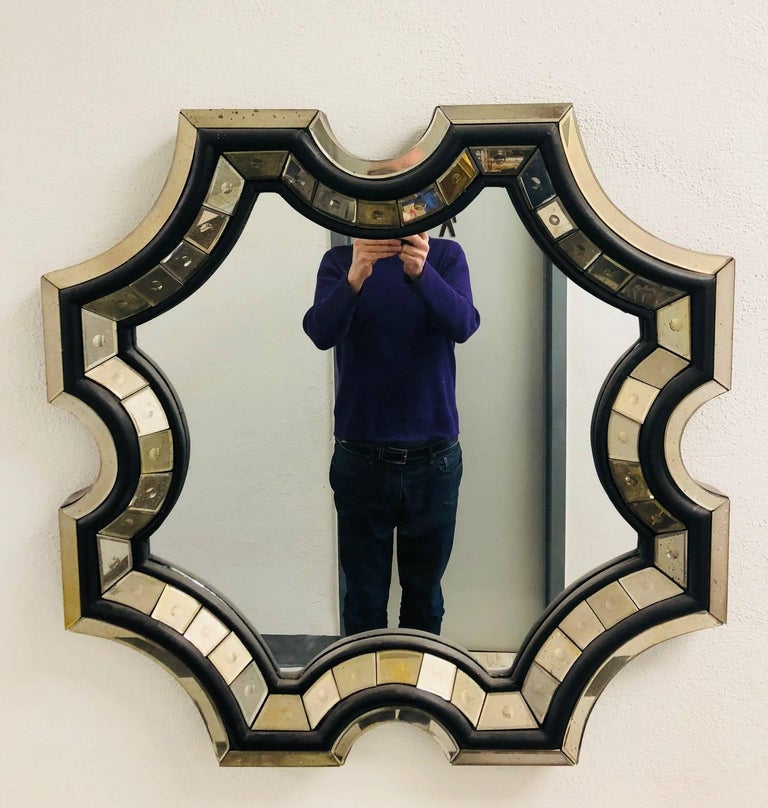 Elegant pair of handmade, French octagonal shaped / sunburst wall mirrors with modern and Neo-Baroque influence. The mirrors have an ebonized wood frame and lined with antiqued faceted mirror plates surrounding an antiqued central mirror plate in