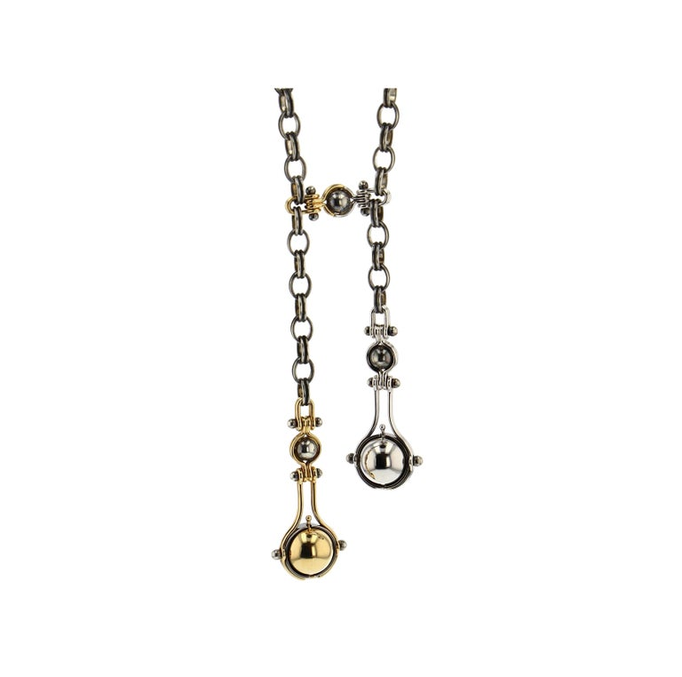 Tie necklace with a patinated silver chain. The two drops are madeof two yellow gold threads around a patinated silver globe supporting a mobile structure. It supports a rotating yellow gold sphere which reveals, on one side a white diamonds bead,