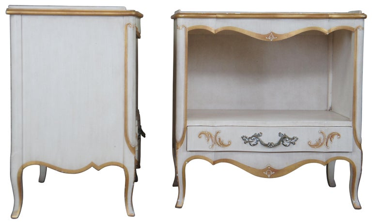 Pair of John Widdicomb Nighstands, circa 1960s. Drawing inspiration from Italian Florentine and Provincial. Features a rectangular form with serpentine front, central cubby, lower drawer and cabriole legs. Finished in antique white with gold