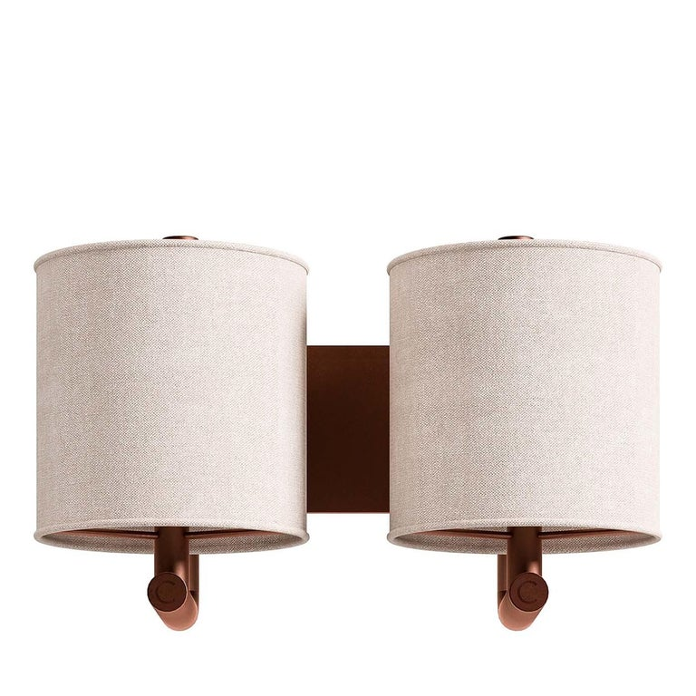 Merging traditional lines with a vintage decorative touch, this wall sconce is a versatile illumination that will fit in a traditional and midcentury decor. Two curved arms extend from a rectangular wall plate in metal with a brushed-copper finish,