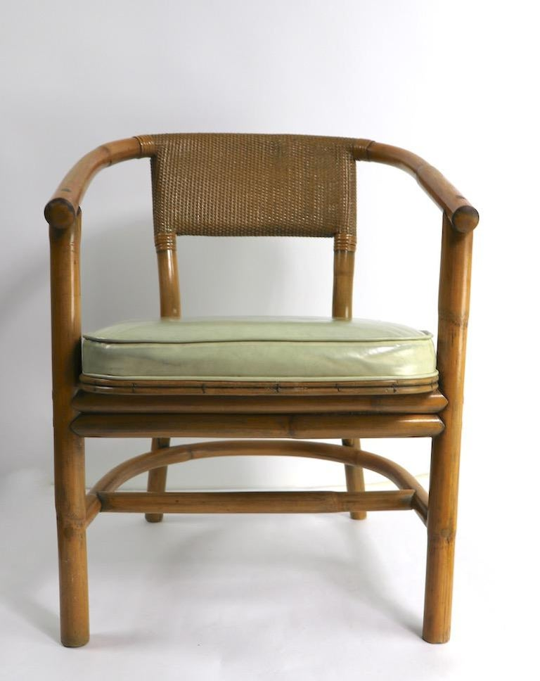 Stylish bamboo arm, lounge chairs, attributed to McGuire. Bamboo frames, with vinyl upholstered seats, and caned backrests. Both are in very good original condition, showing only light cosmetic wear, normal and consistent with age. Total H 30 x arm