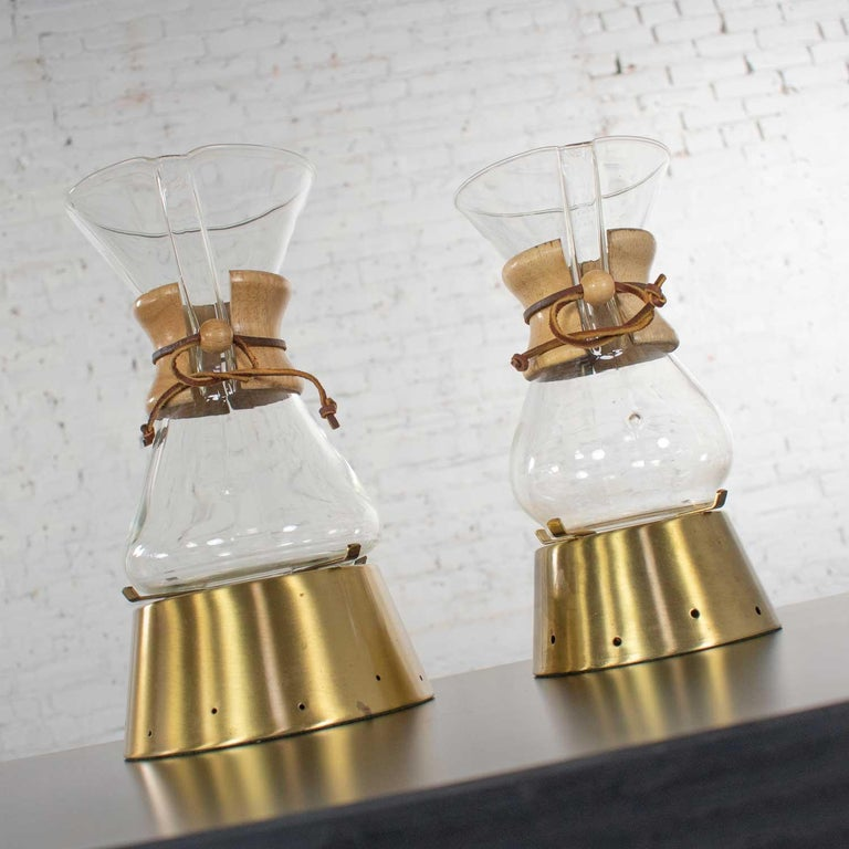 Amazing pair ofMid-Century Modern Chemex pour over coffeemakers designed by Peter Schlumbohm and 2 vintage brass warmers. This pair consists of a 6 cup and 8 cup capacity carafe. They are in wonderful vintage condition. The wood collars do show