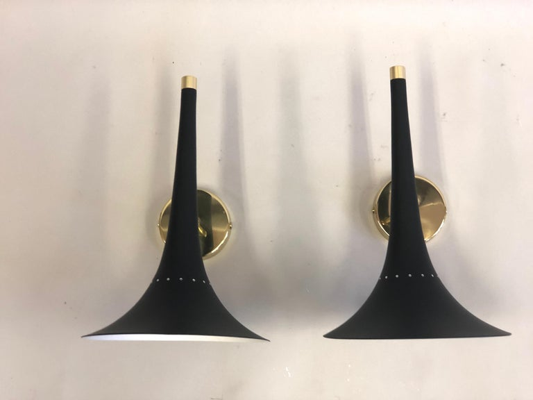 2 pairs of Italian Mid-Century Modern black enameled metal and brass wall lights attributed to Stilnovo. The black enameled metal reflector is delicately tapered ending in a flared oval form from which light is emitted. 1 candelabra socket.  The