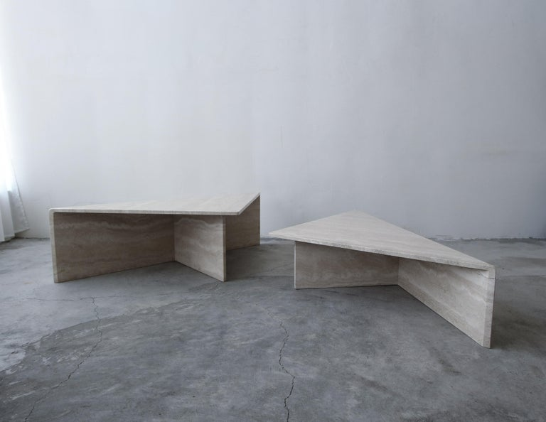 Classic Postmodern tiered Italian travertine coffee table. Simple beautiful piece. Table is of modernist and minimal design, comprised of 2 triangular tables of different heights, they can be configured in any manner to form a square or a rectangle,