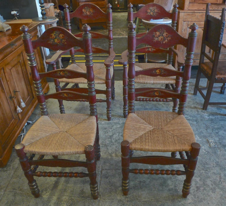 2 Portuguese 19th century hand painted ladder back dining chairs with rush seat and painted flower motif.