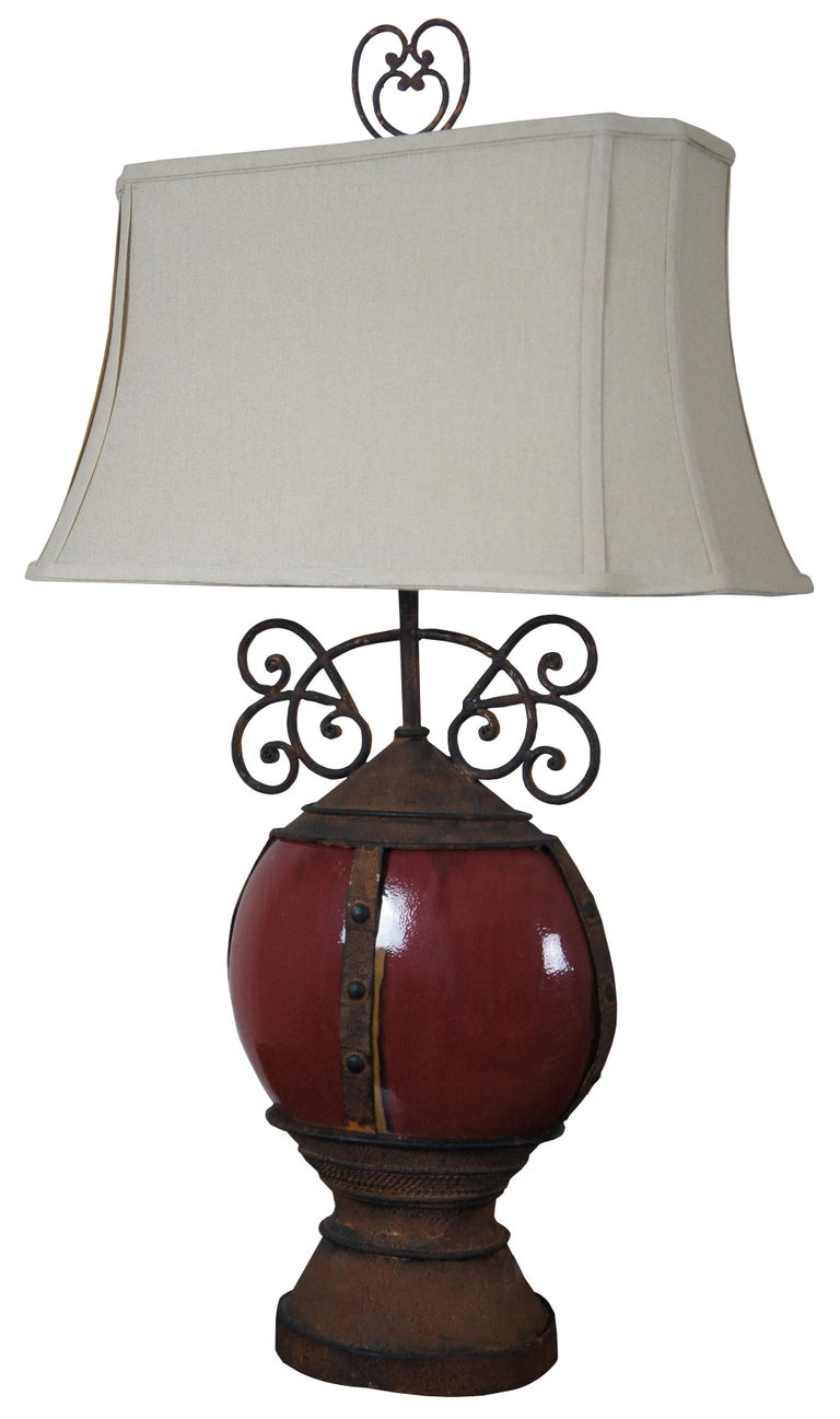 """Pair of rustic round oxblood ceramic table lamps with iron bands, bases and scrolled accents.  Measures: Shade 20.5"""" x 10"""" x 10.75"""", height to top of finial 34""""."""