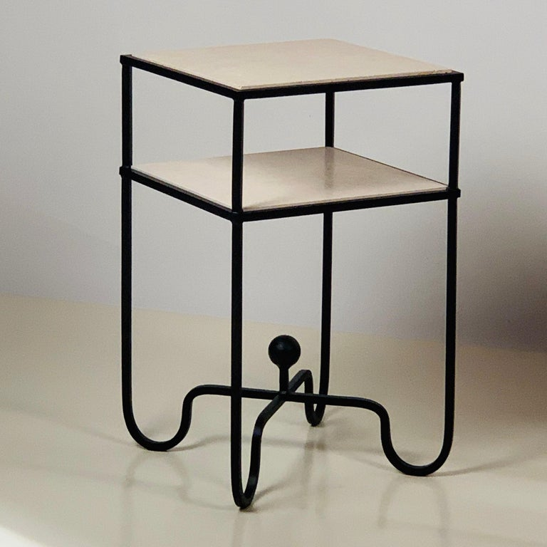2-tier 'Entretoise' side table by Design Frères. Wrought iron base with 2 thin travertine shelves. Shelves are removable for secure shipping and cleaning.