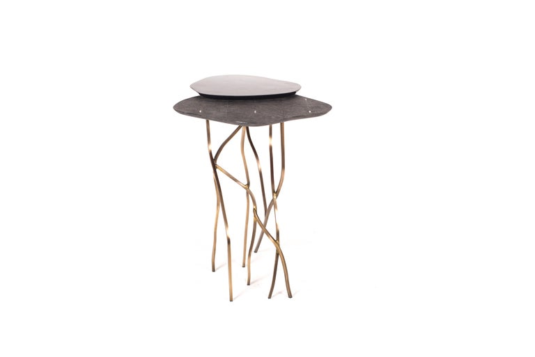 The 2-top floating acacia side table in black shagreen and black pen shell is a beautiful and organic accent piece. A whimsical and airy side table with it's delicate cluster of bronze-patina brass legs sitting beneath the amorphous shaped 2-top.