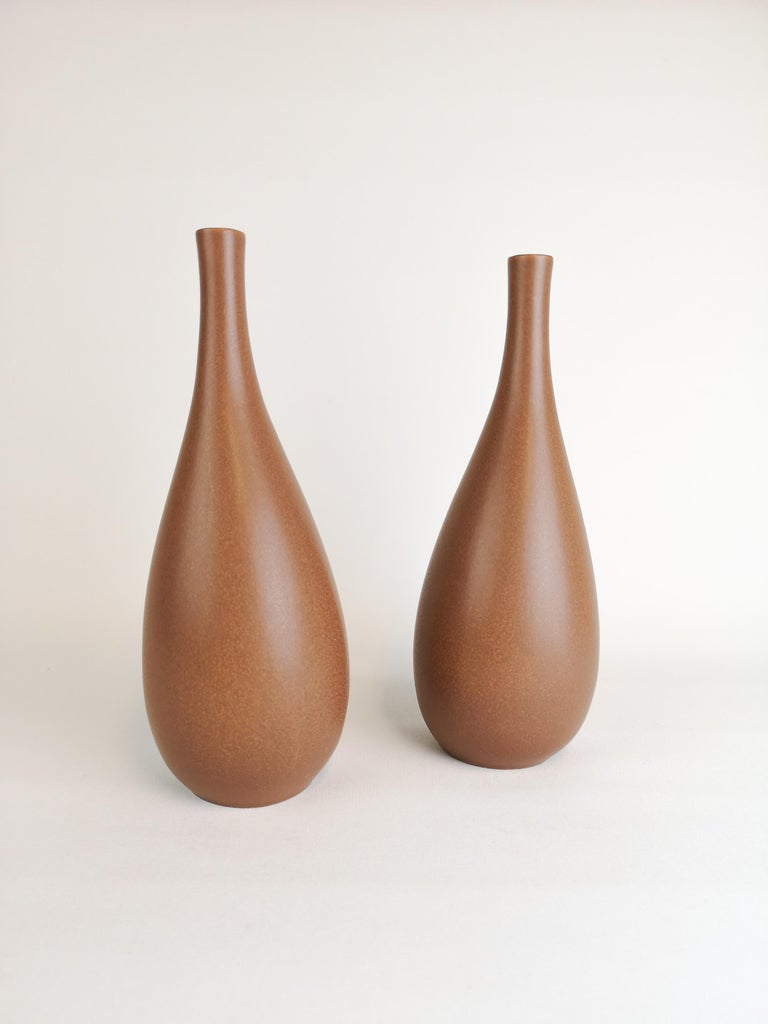 Two nicely shaped vases produced in Sweden and Gustavsberg. The designer Stig Lindberg is excellent in the way he has made the forms of the vases. Stig Lindberg's striking vase with swelling form and semi-matte brown glaze. Elegant midcentury